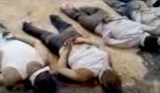 This image made from amateur video released by the Shaam News Network and accessed May 29, 2012, purports to show 13 blindfolded and handcuffed bodies on the ground in Deir el-Zour, Syria. (Associated Press/Shaam News Network via AP video)