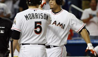 Miami Marlins' Giancarlo Stanton, right, is greeted by Logan Morrison after hitting a solo home run off Washington Nationals pitcher Ryan Perry in the seventh inning in Miami on Wednesday, May 30, 2012. The Nats lost 5-3. (AP Photo/Jeffrey Boan)
