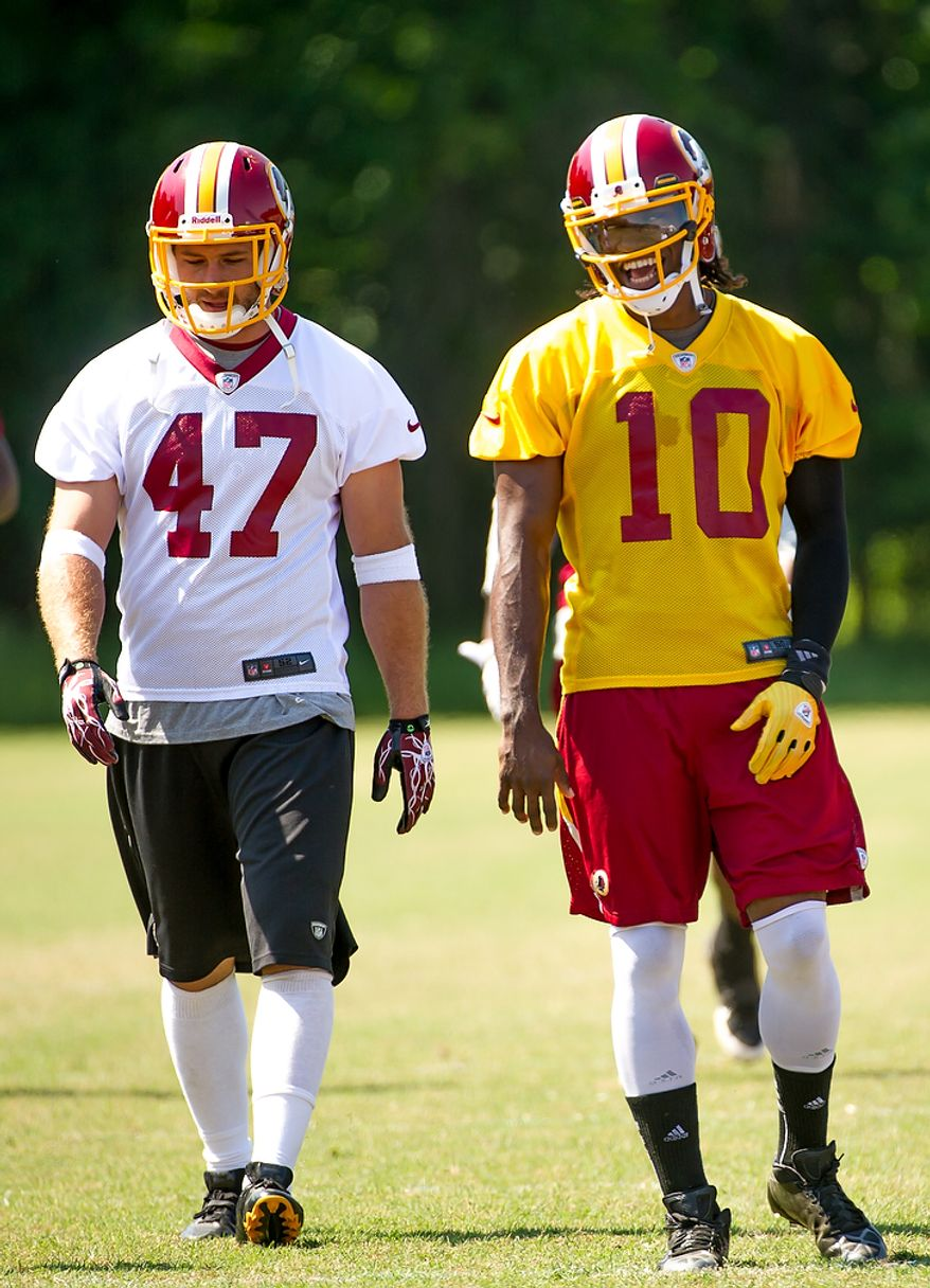 Washington Redskins tight end Chris Cooley (47), left, and Washington Redskins quarterback Robert Griffin III (10), right, share a laugh as they warm up before an organized team activity at Redskins Park, Ashburn, Va., Thursday, May 31, 2012. (Andrew Harnik/The Washington Times)