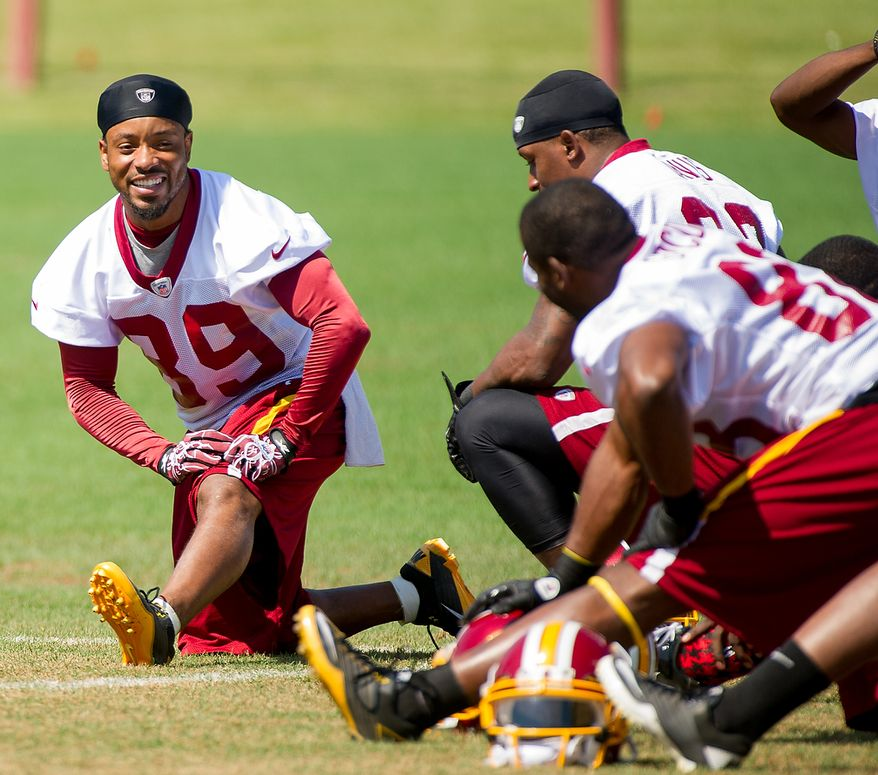 Washington Redskins wide receiver Santana Moss (89), left, shares a laugh with teammates during warm ups before organized team activity at Redskins Park, Ashburn, Va., Thursday, May 31, 2012. (Andrew Harnik/The Washington Times)