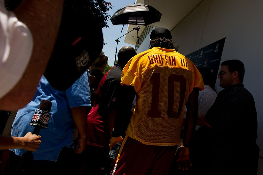 Washington Redskins quarterback Robert Griffin III (10) comes to the podium to answer questions from members of the media following an organized team activity at Redskins Park, Ashburn, Va., Thursday, May 31, 2012. (Andrew Harnik/The Washington Times)