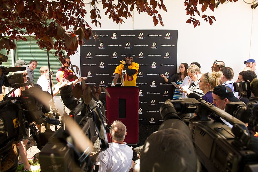 Washington Redskins quarterback Robert Griffin III (10) answers questions from members of the media following an organized team activity at Redskins Park, Ashburn, Va., Thursday, May 31, 2012. (Andrew Harnik/The Washington Times)