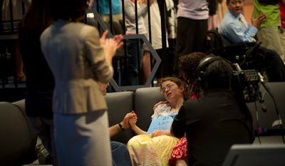 Lena Greenberg, 14, of Philadelphia, falls back on a couch at the side of the stage and is comforted by her mother Marisol Villamil (right) and father David Greenberg (left) after being eliminated from the championship finals of the 2012 Scripps National Spelling Bee at the Gaylord National Resort and Convention Center in Oxon Hill, Md., Thursday, May 31, 2012. (Rod Lamkey Jr/The Washington Times)