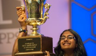 Snigdha Nandipati, 14, (right) of San Diego, Calif., gets help holding up the trophy from her brother Sujan (left) as she wins the 2012 Scripps National Spelling Bee at the Gaylord National Resort and Convention Center in Oxon Hill, Md., Thursday, May 31, 2012. (Rod Lamkey Jr/The Washington Times)