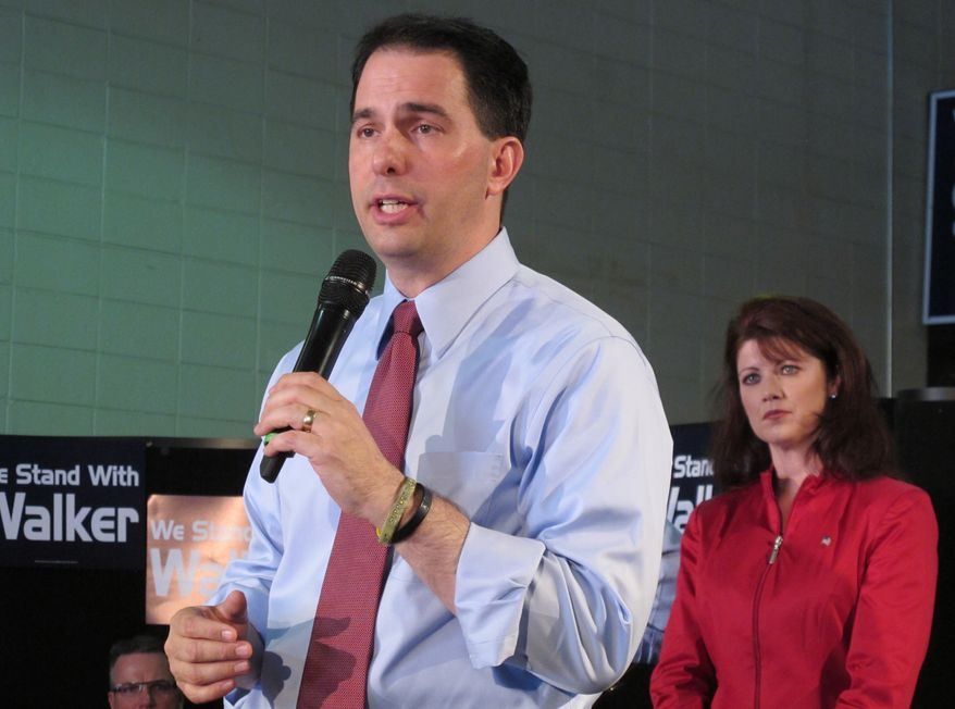 Wisconsin Gov. Scott Walker, shown with Lt. Gov. Rebecca Kleefisch, has tea party support as he faces a recall vote. (Associated Press)
