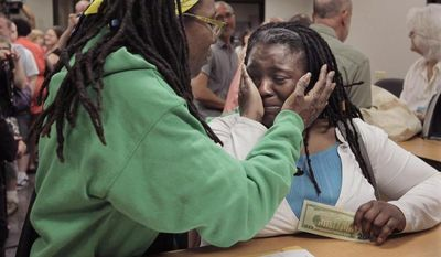 Janean Watkins (left) and Lakeesha Harris embrace after being the first in line to obtain a civil union license from the Cook County Office of Vital Records in Chicago on Wednesday, June 1, 2011. (AP Photo/M. Spencer Green)