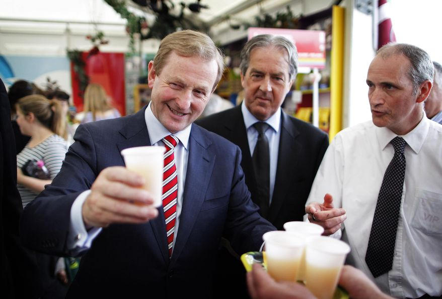 """Irish Prime Minister Enda Kenny takes a glass of apple juice at the Bord Bia Bloom festival in the Phoenix Park, Dublin, on June 1, 2012. Referendum officials compiling unofficial results say Ireland's voters have decided to ratify the European Union's deficit-fighting treaty with """"yes"""" votes reaching nearly 60 percent. (Associated Press)"""