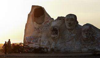 Men walk May 23, 2012, near a statue showing the defaced likeness of ousted Egyptian President Hosni Mubarak (left), Egyptian Nobel prize winner Ahmed Zewail (second left), late Egyptian President Anwar Sadat (second right) and Egyptian novelist and Nobel Prize Winner Naguib Mahfouz, in 6th of October City, Egypt. (Associated Press)