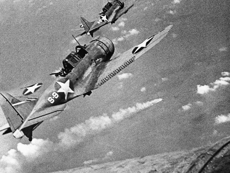 Two U.S. dive bombers fly over a burning Japanese ship during the battle of Midway on June 7, 1942. Under the incessant pounding of American fliers, 20 ships of the enemy armada of 80 were sunk or damaged and the others put to flight. (Associated Press)