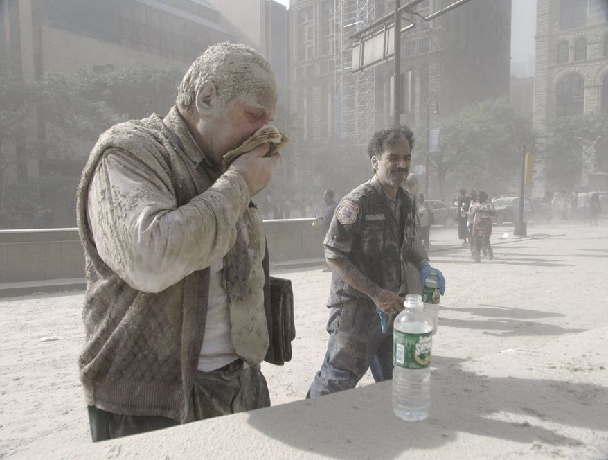 **FILE** A man wipes ash from his face Sept. 11, 2001, after terrorists flew two airplanes into the World Trade Center towers, causing them to collapse. (Associated Press)