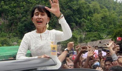 Myanmar's opposition leader Aung San Suu Kyi waves from a vehicle to cheering Karen refugees as she tours Mae La refugee camp in Tha Song Yang district, Tak province, northern Thailand, Saturday, June 2, 2012. (AP Photo/Wason Wanichakorn)