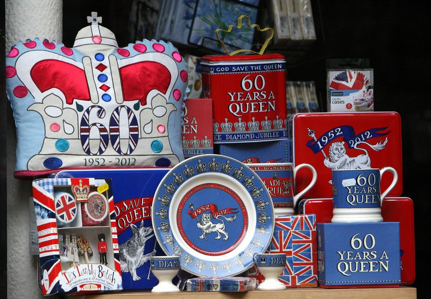 A member of the public is seen walking past a shop window with a display in honor of Britain's Queen Elizabeth II Diamond Jubilee in Durham, England, Thursday, May 31, 2012. AP Photo/Scott Heppell)