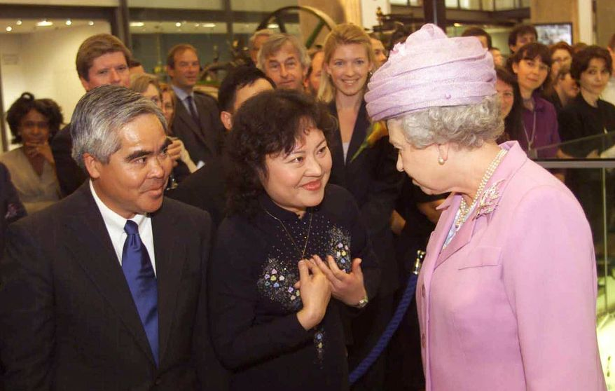 ** FILE ** In this Tuesday, June 27, 2000, file photo, Britain's Queen Elizabeth II, right, opens the new Wellcome Wing of London 's Science Museum with Associated Press photographer Nick Ut, left and Phan Thi Kim Phuc, center. Phuc was the main subject in Ut's iconic image of the aftermath of a June 8, 1972, napalm attack in Vietnam. The image is featured in the museum. (AP Photo/Ian Jones, Pool)