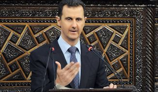 Syrian President Bashar Assad delivers a speech in Damascus on Sunday. He denied responsibility for the massacre in Houla last month. (Associated Press)