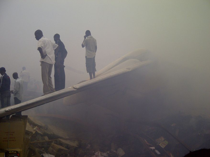 Onlookers stand on the tail wing of a crashed passenger plane in a neighborhood just north of Murtala Muhammed International Airport in Lagos, Nigeria, on Sunday, June 3, 2012. (AP Photo/Jon Gambrell)