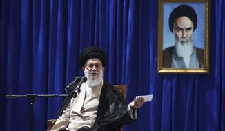 Ayatollah Ali Khamenei, Iran's supreme leader, speaks during a ceremony marking the 23rd anniversary of the death of Iran's revolutionary founder, Ayatollah Khomeini (shown in the poster at right), at his mausoleum outside Tehran on Sunday, June 3, 2012. (AP Photo/Mohammad Hassanzadeh, Fars News Agency)
