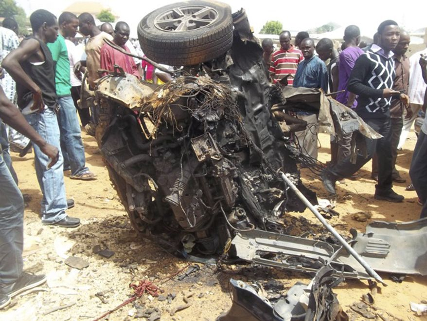 People gather around a car used by a suicide bomber following an explosion in a church compound in Bauchi, Nigeria, on Sunday, June 3, 2012. (AP Photo/Shehu Saulawa)