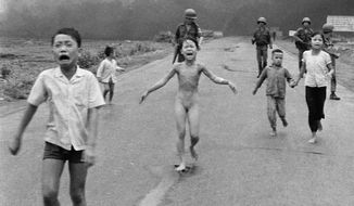 Nine-year-old Kim Phuc (center) runs down Route 1 near Trang Bang, Vietnam, on June 8, 1972, after an accidental aerial napalm attack as South Vietnamese forces from the 25th Division walk behind. With her (from left) are her younger brothers Phan Thanh Tam, who lost an eye, and Phan Thanh Phouc and her cousins Ho Van Bon and Ho Thi Ting. (AP Photo/Nick Ut)