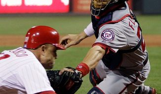 Washington Nationals catcher Jesus Flores, right, tags out Philadelphia Phillies' Placido Polanco at home after Polanco tried to score on a fielder's choice by Phillies' Carlos Ruiz in the sixth inning of a baseball game, Monday, May 21, 2012, in Philadelphia. (AP Photo/Matt Slocum)