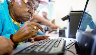 """Mary Plush, 85, learns how to type an email in a course teaching senior citizens the ins and outs of the Internet. """"The computer helps stimulate your mind,"""" says Maelene Johnson, another resident at Garfield Terrace in Northwest. (Andrew Harnik/The Washington Times)"""