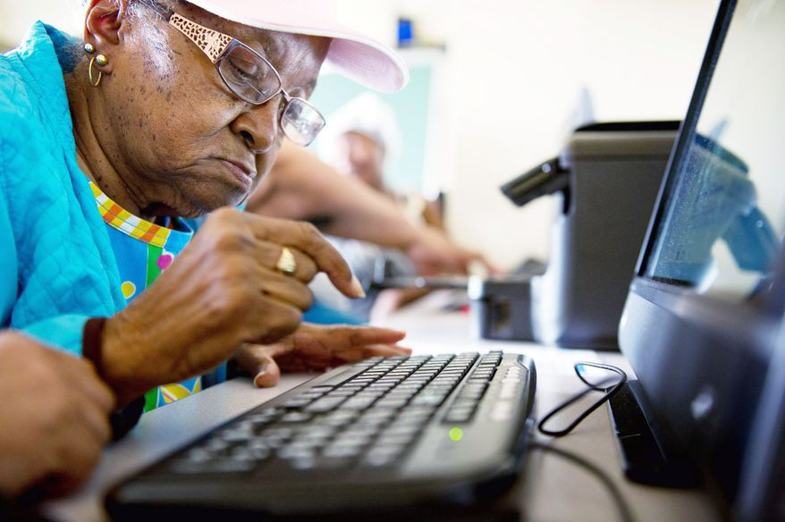 "Mary Plush, 85, learns how to type an email in a course teaching senior citizens the ins and outs of the Internet. ""The computer helps stimulate your mind,"" says Maelene Johnson, another resident at Garfield Terrace in Northwest. (Andrew Harnik/The Washington Times)"