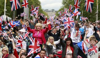 Members of the public sit June 4, 2012, on the Mall  in London while waiting for the start of a pop music concert at Buckingham Palace to help celebrate Britain's Queen Elizabeth II's 60-year reign during Diamond Jubilee celebrations. (Associated Press)