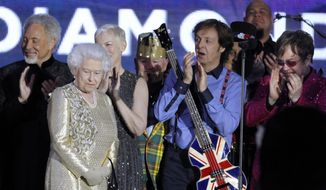 Britain's Queen Elizabeth II, 2nd from left, is joined on stage by performers Sir Tom Jones, Annie Lennox, Sir Paul McCartney and Sir Elton John at the conclusion of the Queen's Jubilee Concert in front of Buckingham Palace, London, Monday, June 4, 2012. The concert is a part of four days of celebrations to mark the queen's 60-year reign. (AP Photo/Joel Ryan)