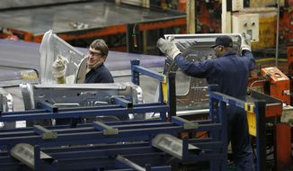 ** FILE ** Auto workers at the Ford Stamping Plant in Chicago Heights, Ill., stack the inner door panel for a Ford Explorer on Wednesday, April 4, 2012. (Associated Press)