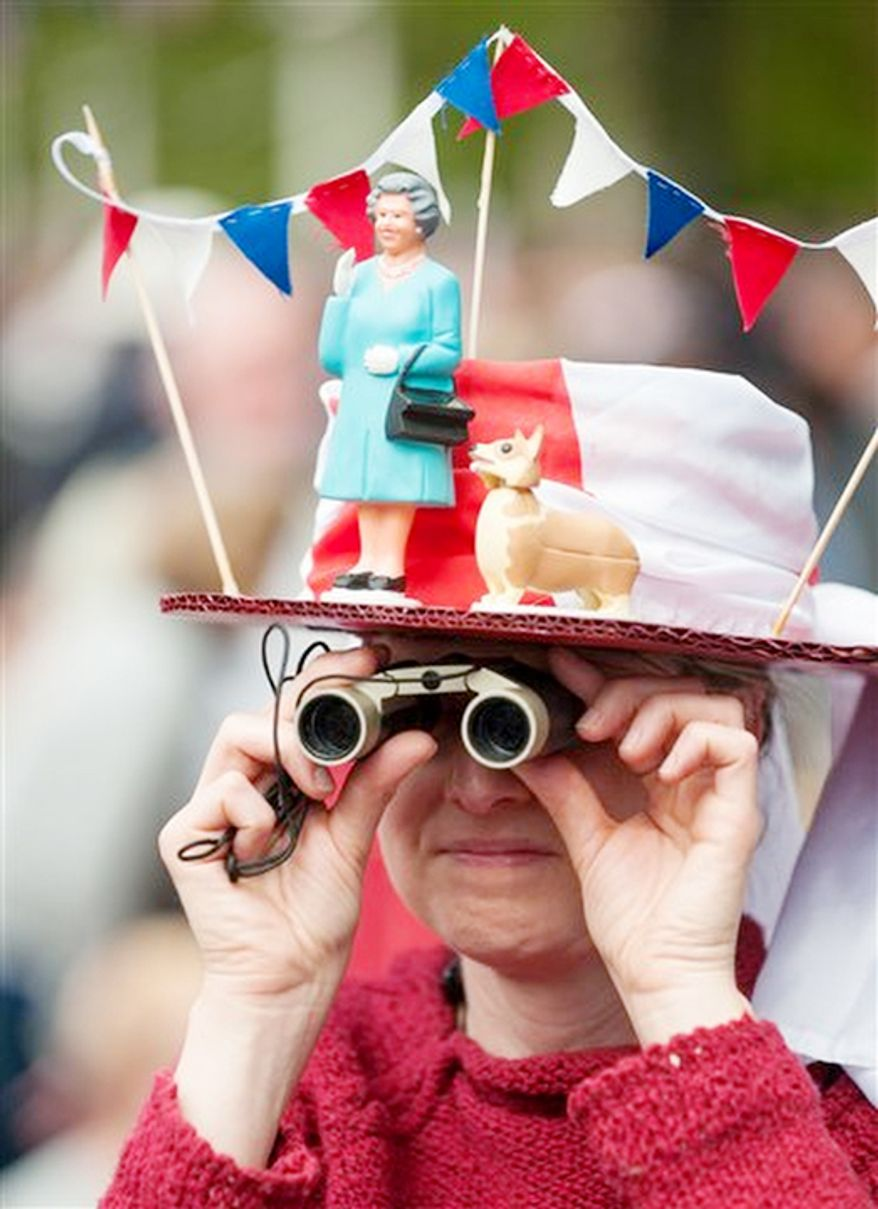 A woman in a fancy dress hat featuring Queen Elizabeth II and a corgi waits for the start of the  Diamond Jubilee concert in London Monday June 4, 2012.  But the queen's husband, Prince Philip, missed the concert after being hospitalized with a bladder infection. (AP Photo / Dominic Lipinski, Pool)