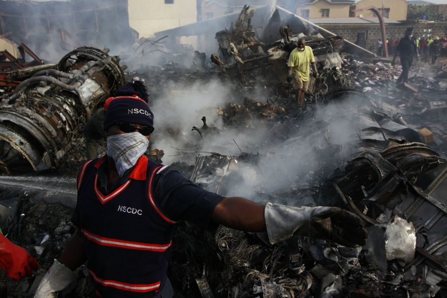 Rescue workers search for bodies at the site of a plane crash in Lagos, Nigeria, on Monday, June 4, 2012. (AP Photo/Sunday Alamba)