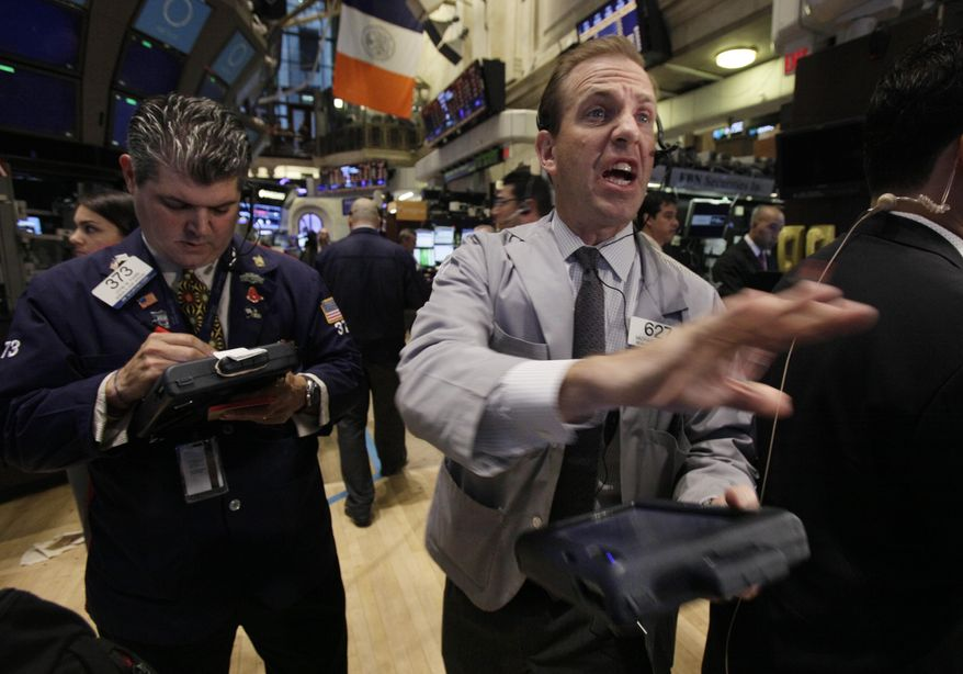 Traders John Panin (left) and Michael Smyth work June 4, 2012, on the floor of the New York Stock Exchange. (Associated Press)