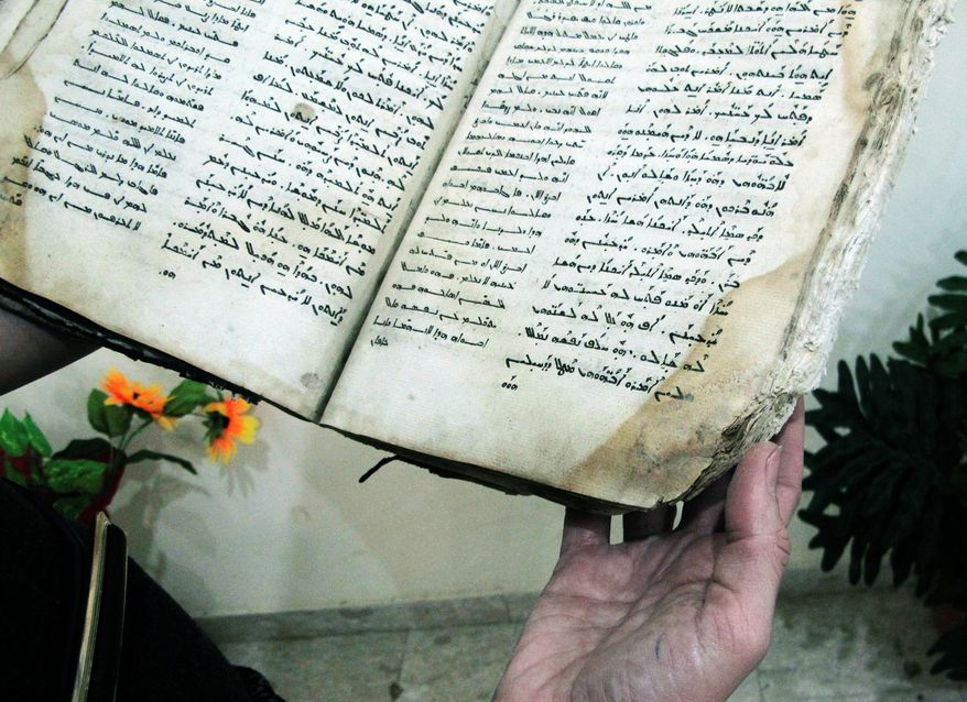 In a Wednesday, May 2, 2012 photo Atif Zarka, 64, a volunteer Aramaic teacher's assistant holds a copy of the Gospel of Luke in Aramaic script in the Arab village of Jish, northern Israel. Jish is one of two villages in the Holy Land's tiny Christian community that are teaching Aramaic to their children in an ambitious effort to preserve the language that Jesus spoke, centuries after it all but disappeared from the modern Middle East. (AP Photo/Diaa Hadid)