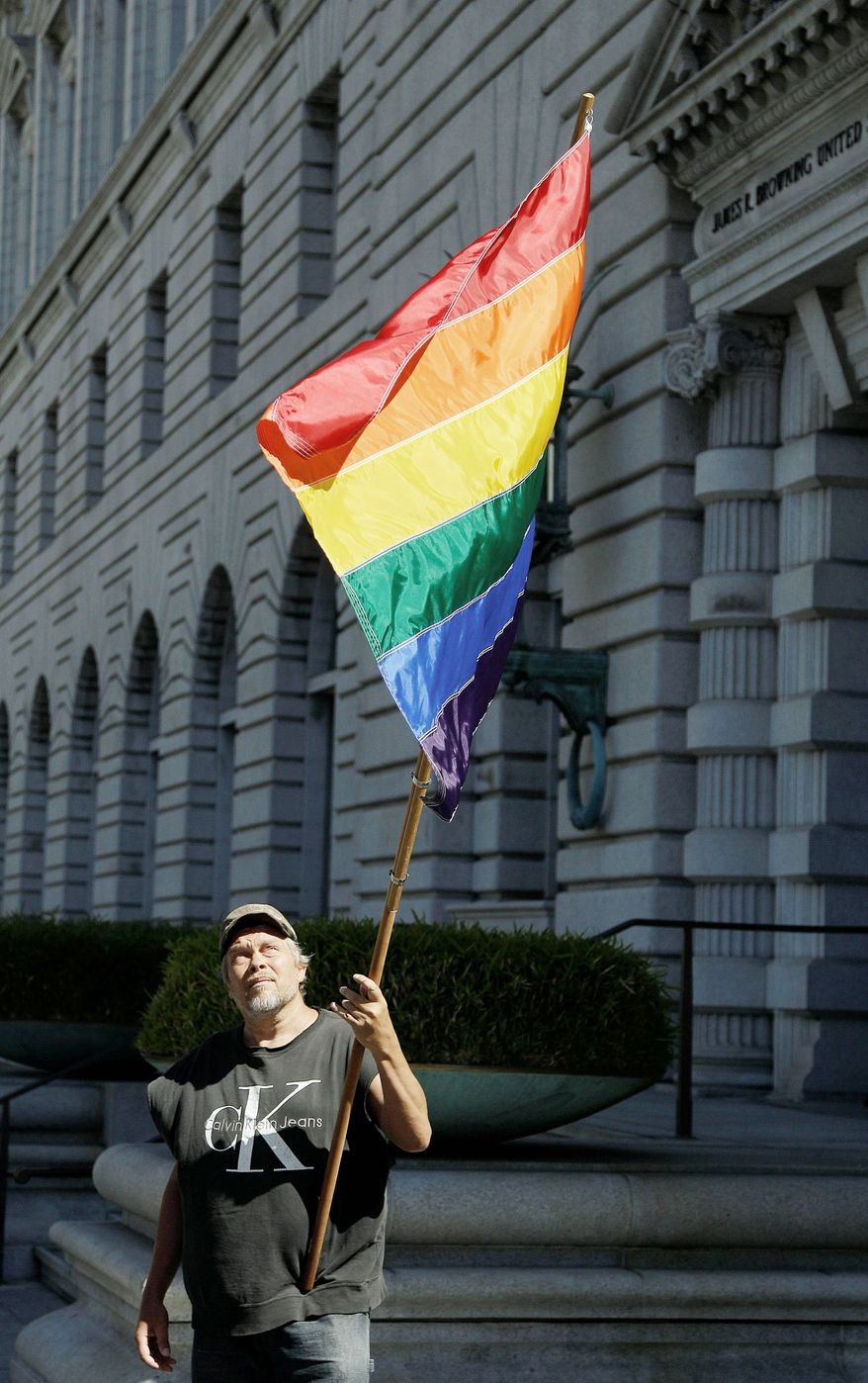 ** FILE ** In this June 5, 2012, file photo, gay marriage supporter Bob Sodervick holds a flag outside the 9th U.S. Circuit Court of Appeals in San Francisco. (Associated Press)