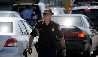 **FILE** A U.S. Customs and Border Protection officer walks through a line of cars at a crossing from Canada near Blaine, Wash., on July 21, 2009. (Associated Press)