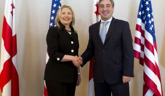 Georgian Prime Minister Nika Gilauri (right) greets U.S. Secretary of State Hillary Rodham Clinton before their meeting in Batumi, Georgia, on Tuesday, June 5, 2012. (AP Photo/Saul Loeb, Pool)