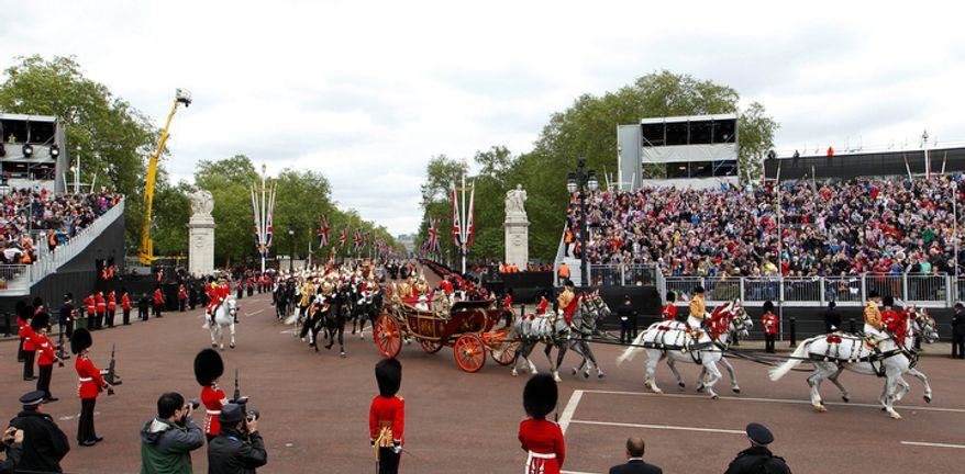 Britain's Queen Elizabeth II travels with Prince Charles and Camilla, Duchess of Cornwall in a horse drawn carriage returning to Buckingham Palace in London. (AP Photo/Sang Tan)