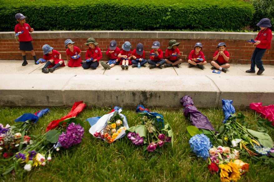 """British School of Washington Pre-K students sit down to eat cake near   bouquets of flowers the students helped make which will go out to retirement homes as part of a """"Big Picnic Lunch"""" in celebration of Queen Elizabeth's Diamond Jubilee, Washington, D.C. (Andrew Harnik/The Washington Times)"""