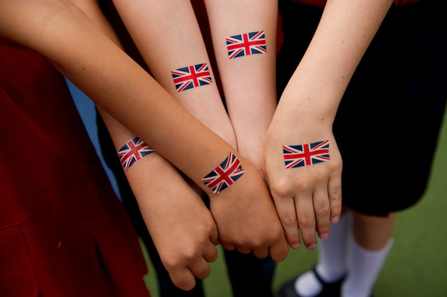 """Students with the British School of Washington get British flag fake tattoos during the school's """"Big Picnic Lunch"""" in celebration of Queen Elizabeth's Diamond Jubilee, Washington, D.C., Tuesday, June 5, 2012. The Diamond Jubilee of Queen Elizabeth II is a celebration of 60 years that the queen has been ruling. (Andrew Harnik/The Washington Times)"""