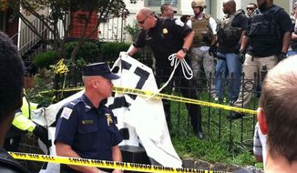 """Officers remove an """"Eviction Free Zone"""" sign from the front yard of a Capitol Hill home, where U.S. Marshals and Occupy protesters clashed Tuesday morning. (Meredith Somers/The Washington Times)"""