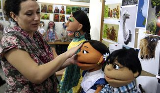 ** FILE ** In a Oct. 13, 2011, file photo, a Pakistani artist, left, gives final touches to characters of Pakistani Sesame Street in Lahore, Pakistan. The U.S. Embassy in Pakistan says it terminated funding for a $20 million project to develop a local version of Sesame Street amid reports of corruption. (AP Photo/K.M.Chaudary, file)