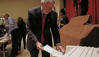 Wisconsin Democratic gubernatorial candidate Tom Barrett puts his ballot into a machine after voting June 5, 2012, in Milwaukee. Barrett is facing Republican Wisconsin Gov. Scott Walker in a recall election. (Associated Press)