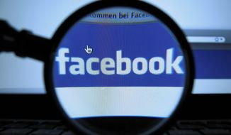 A magnifying glass is posed over a monitor displaying a Facebook page in Munich on Oct. 10, 2011. (Associated Press) ** FILE **