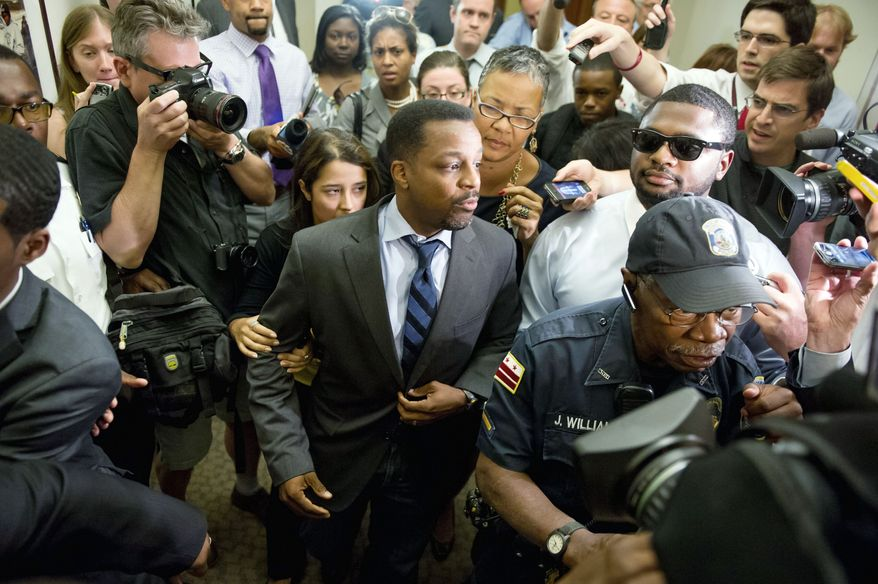D.C. Council Chairman Kwame R. Brown leaves his office at the John A. Wilson Building after being charged Wednesday in federal court with one felony count of bank fraud. He resigned hours later. (Andrew Harnik/The Washington Times)