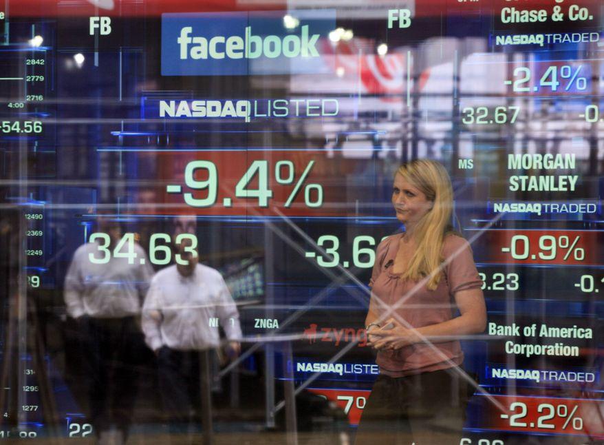 **FILE** Television correspondent Sabrina Quagliozzi reports May 21, 2012, from inside the Nasdaq MarketSite in New York's Times Square. (Associated Press)