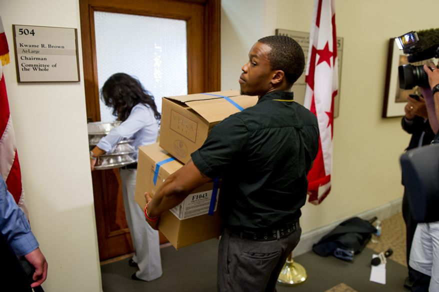 D.C. Council Chairman Kwame Brown's staff members carry food into the chairman's offices at the Wilson Building after being charged with one felony count of bank fraud, Washington, D.C., Wednesday, June 6, 2012.  (Andrew Harnik/The Washington Times)