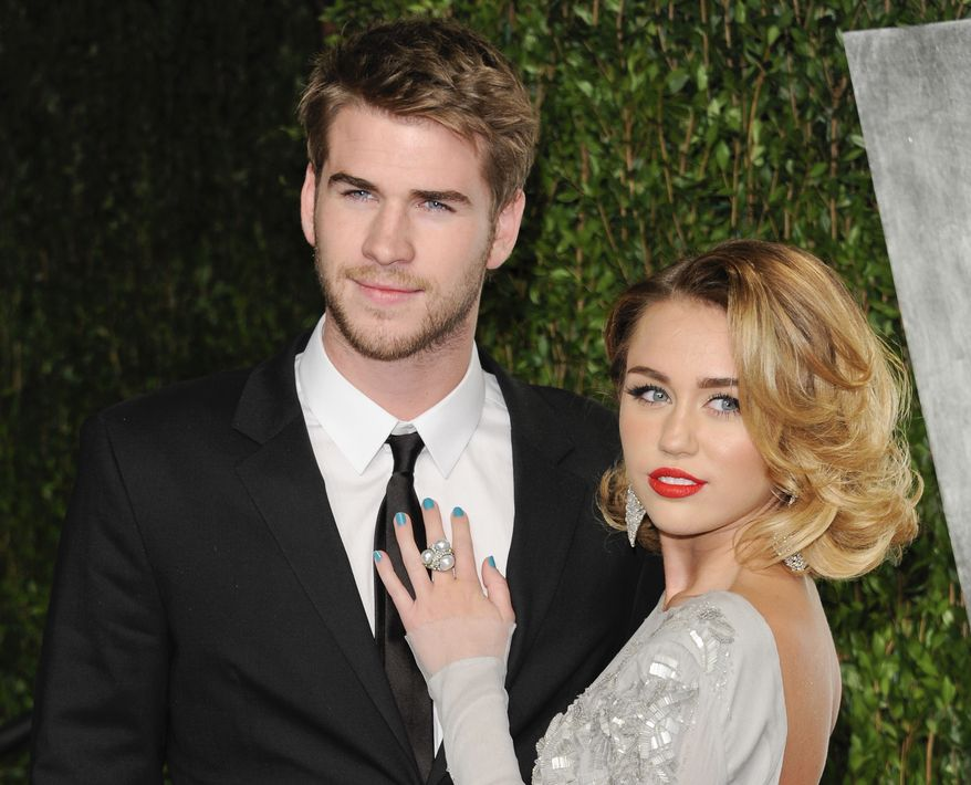 """** FILE ** This Feb. 26, 2012 photo shows Miley Cyrus, right, and Liam Hemsworth at the Vanity Fair Oscar party in West Hollywood, Calif. The couple who met on the set of the movie """"The Last Song"""" in 2009 announced their engagement Wednesday morning. (AP Photo/Evan Agostini, file)"""