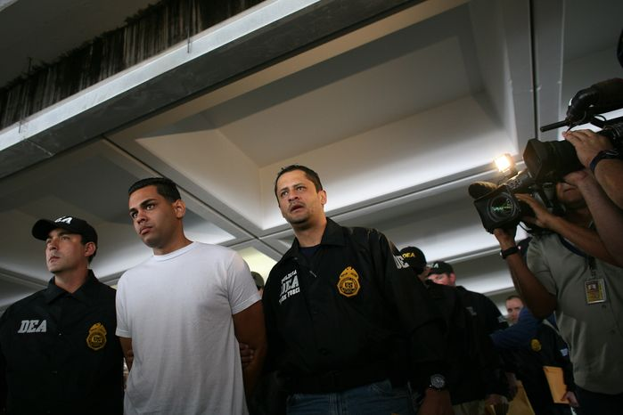 Drug Enforcement Administration officers escort a handcuffed suspect after his arrest on drug smuggling charges in San Juan, Puerto Rico, on Wednesday, June 6, 2012. (AP Photo/Ricardo Arduengo)