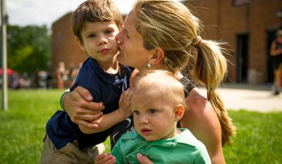 Keli Smith Puzo poses with her two children, Xavi Puzo, 2, right, and Ian Puzo, 9, left, between matches during the Women's National Championships of U.S.A. Field Hockey, College Park, Md., Monday, June 4, 2012. (Andrew Harnik/The Washington Times)