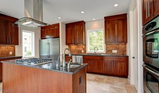 The kitchen, which is open to the dining area and great room, has granite counters and a center island with a five-burner cooktop.