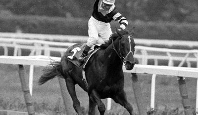 In this June 13, 1997 file photo, jockey Jean Cruguet, aboard Seattle Slew, wins the 1977 Belmont Stakes in Elmont, New York. (AP Photo/File)